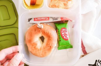 a hand touching a school lunch box with bagel, green tea kitkat, beef jerky, apples and oranges